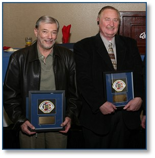 Two reserve officers holding plaques