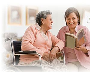 Woman reading to older woman in wheelchair