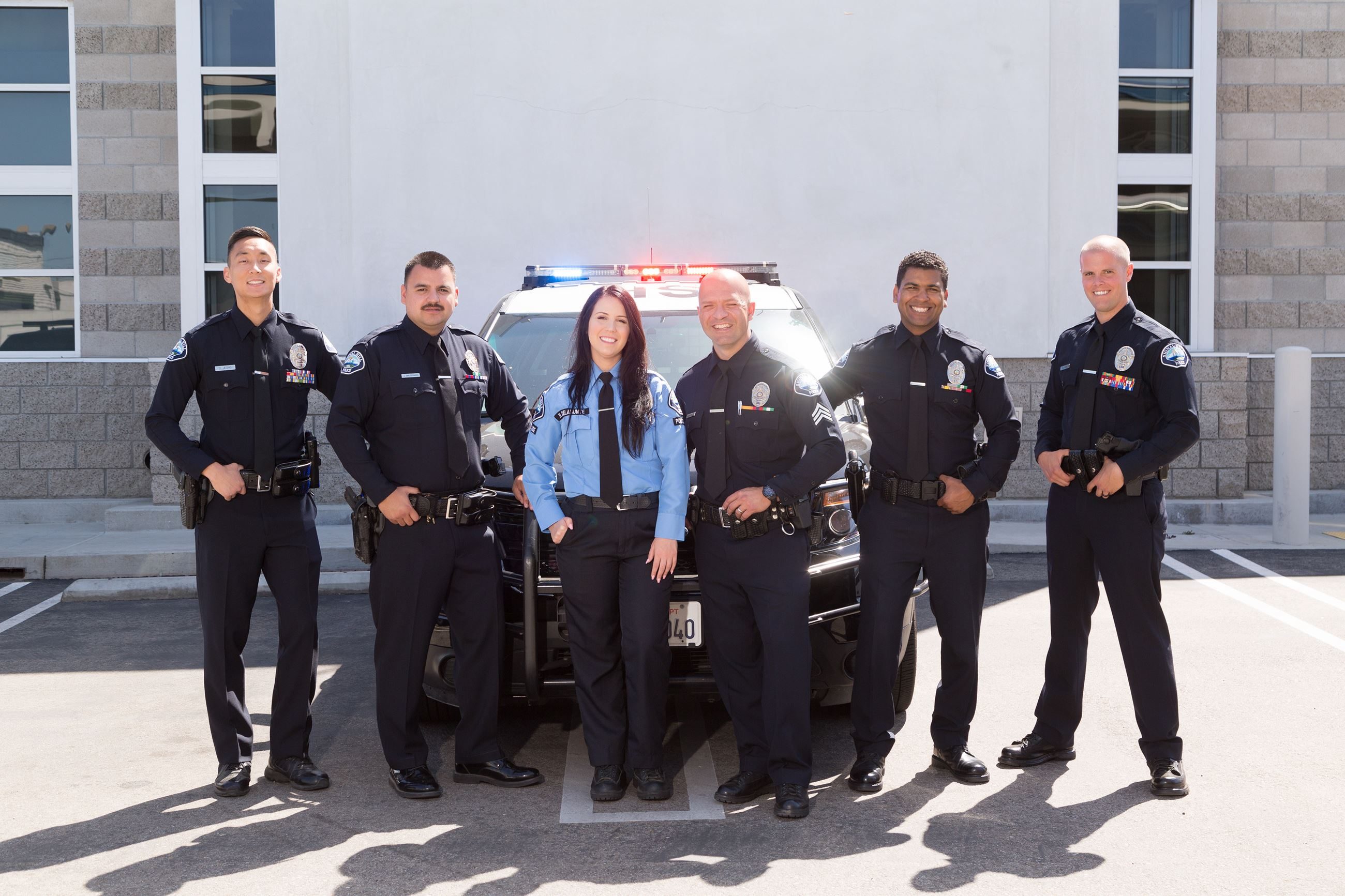 Police Officers Smiling in front of a police car