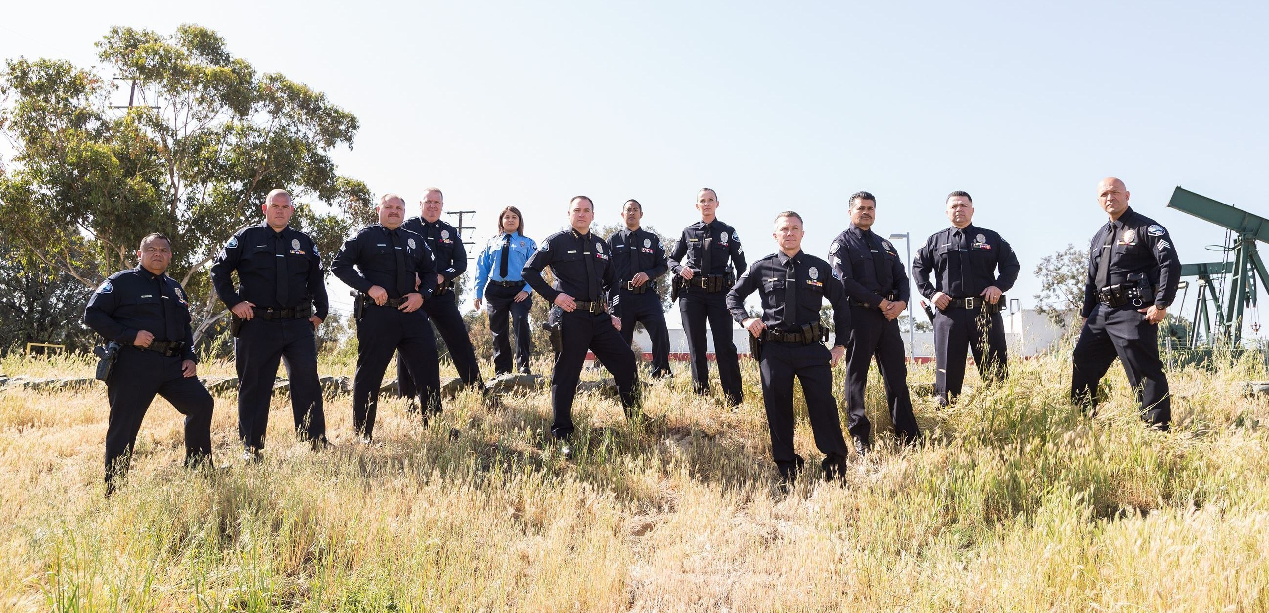 A group of police officers standing in tall grass