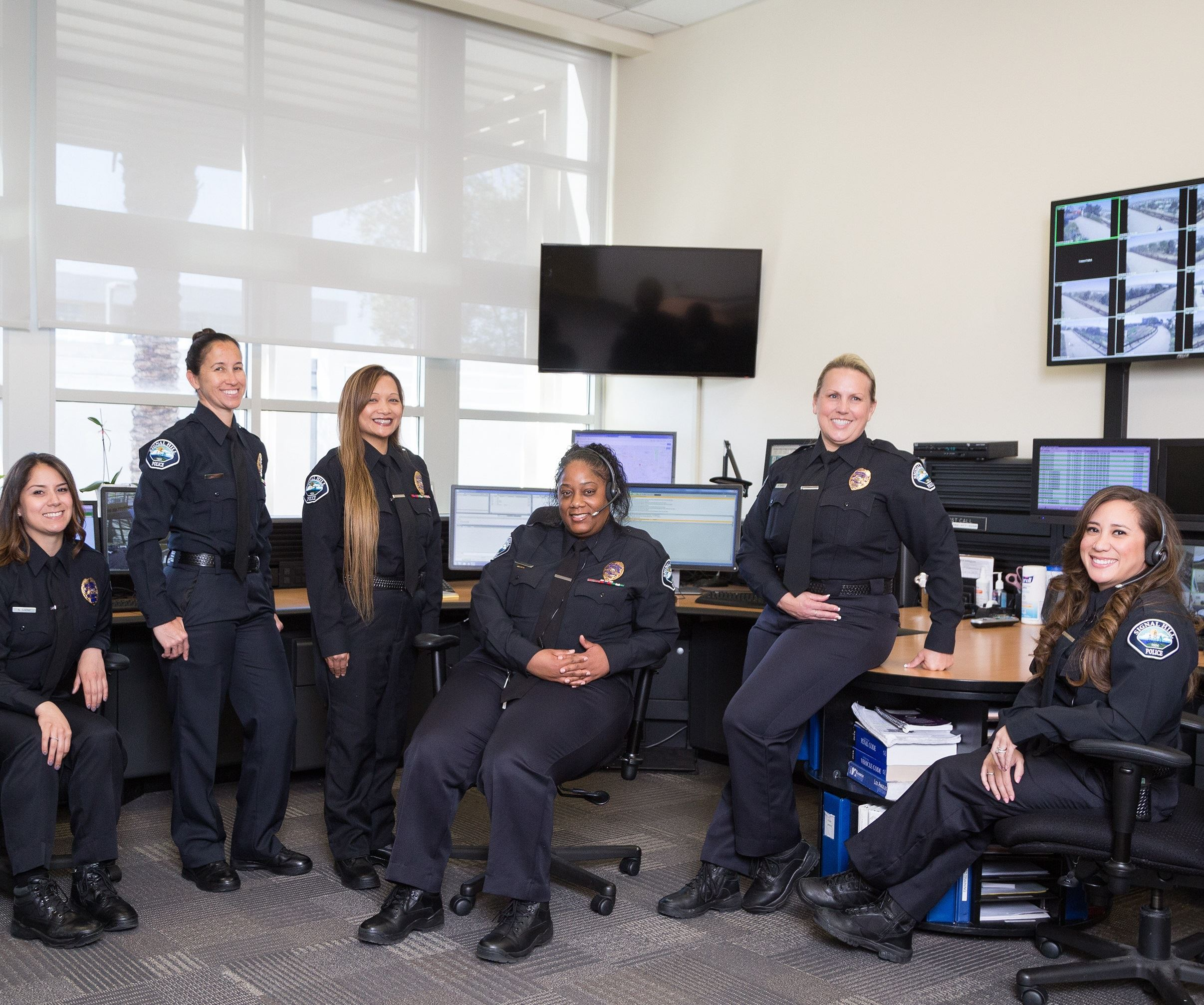 Dispatchers smiling in front of dispatch center