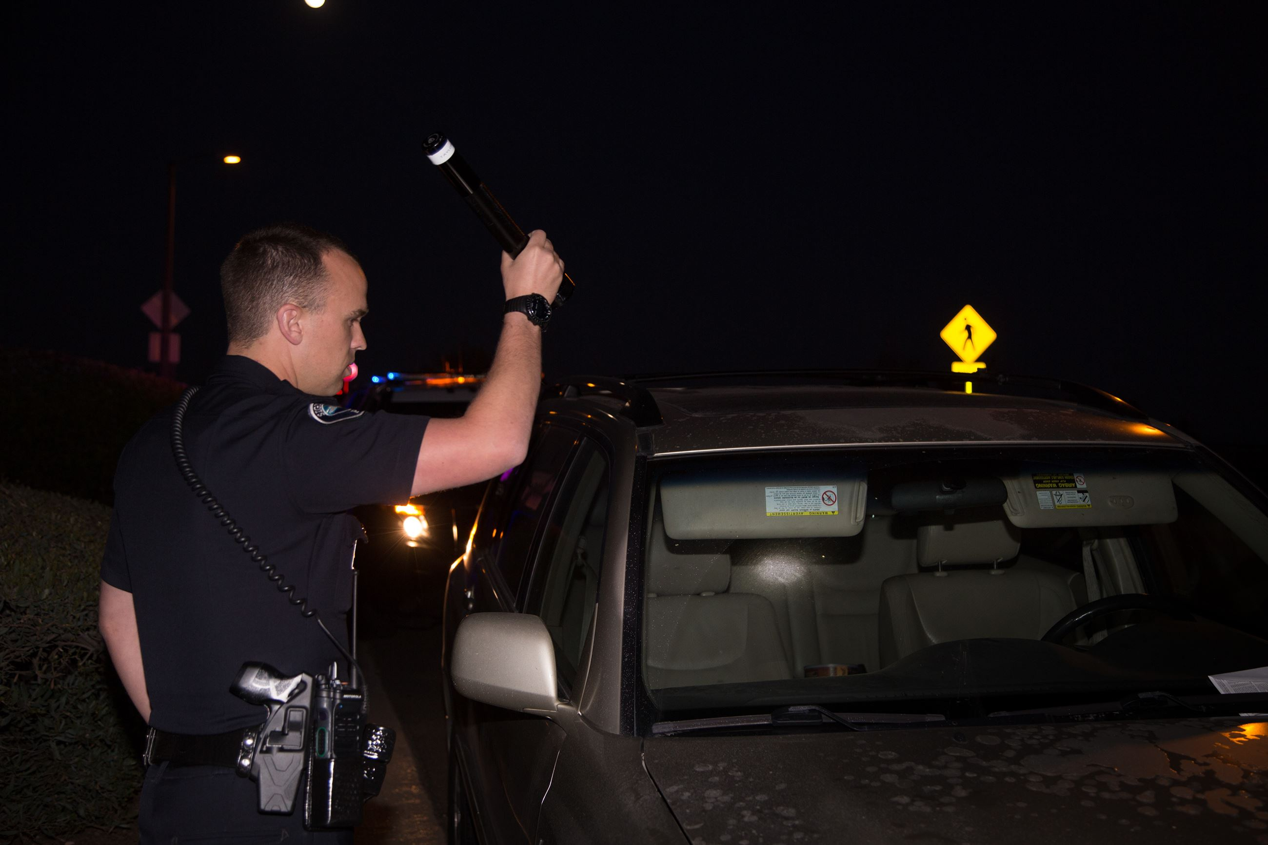 Officer shining a flashlight into a car