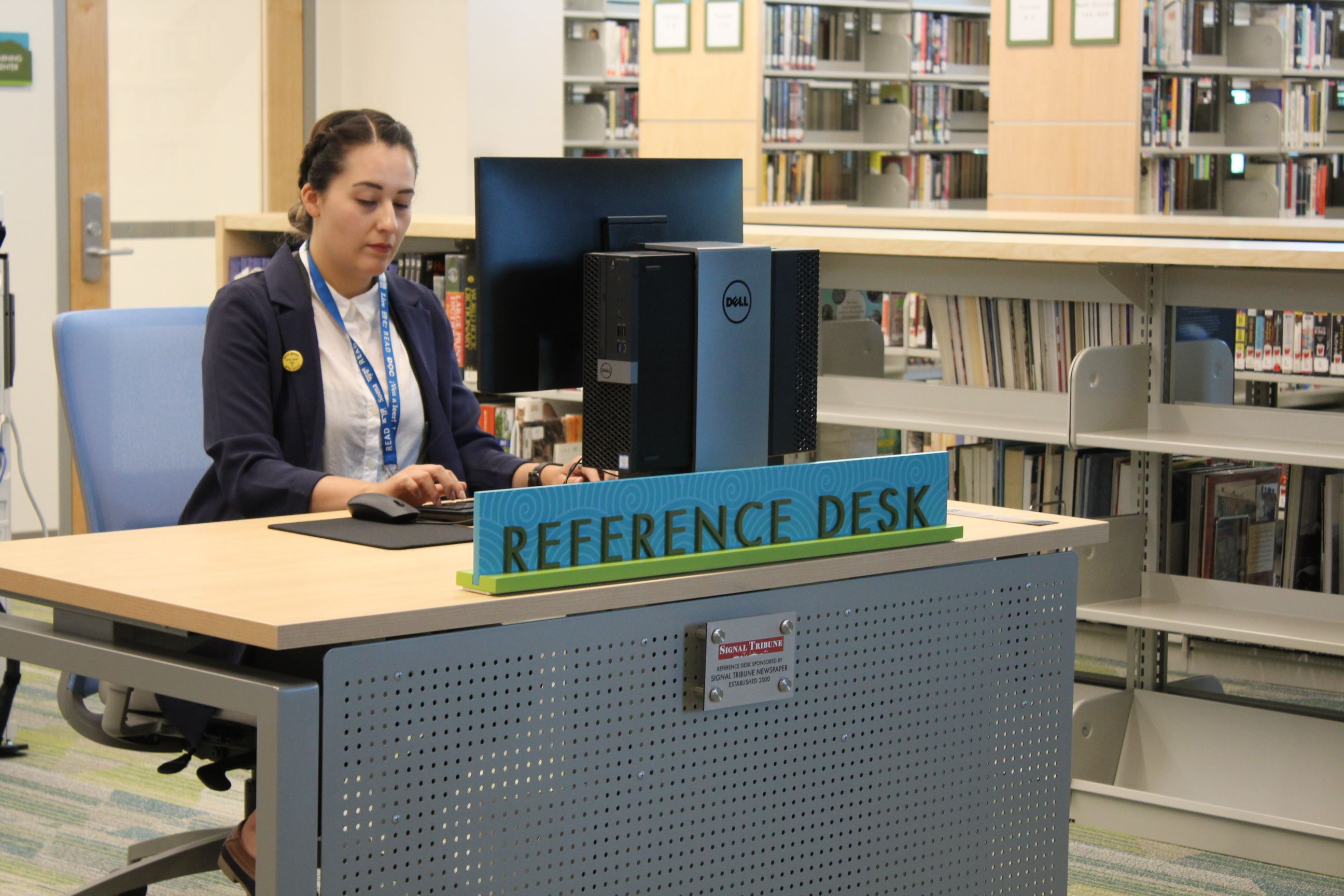 Library Assistant Sitting at Reference Desk